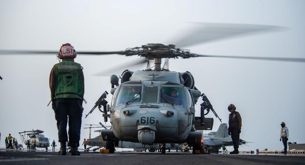 Marinheiros preparam helicóptero MH-60S Sea Hawk, do Esquadrão de Combate Marítimo de Helicópteros (HSC) 12, para iniciar voo do convés do porta-aviões USS Ronald Reagan em resposta a um pedido de assistência do navio Mercer Street no mar Arábico