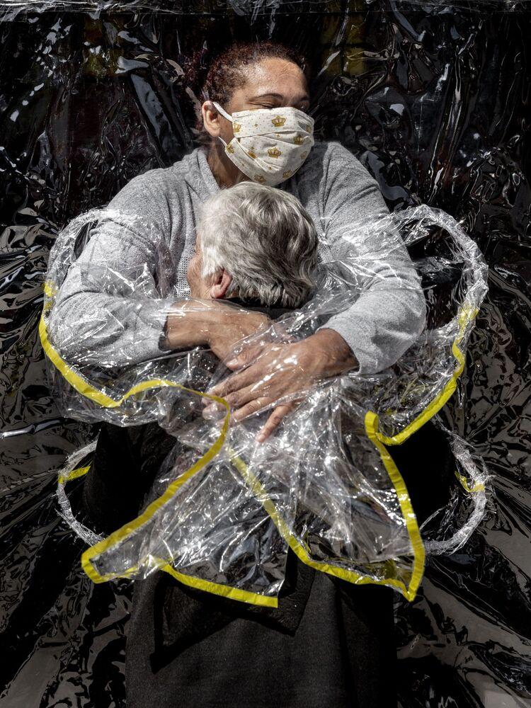 Foto Hugs to Survive (Abraços para Sobreviver, na tradução) do fotógrafo dinamarquês Mads Nissen, que tomou primeiro lugar na categoria Humanidade. Rosa Luzia Lunardi, de 85 anos, é abraçada pela enfermeira Adriana Silva da Costa Souza, o seu primeiro abraço recebido em cinco meses