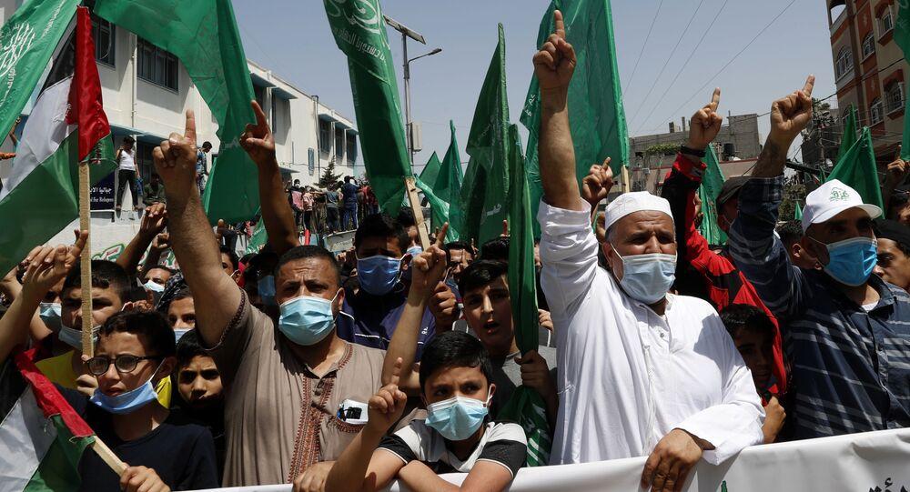 Apoiadores do Hamas usando máscaras acenam bandeiras islâmicas verdes enquanto entoam slogans durante comício em solidariedade aos companheiros palestinos em Jerusalém e contra a decisão do presidente palestino Mahmoud Abbas de adiar as eleições palestinas. Foto de arquivo