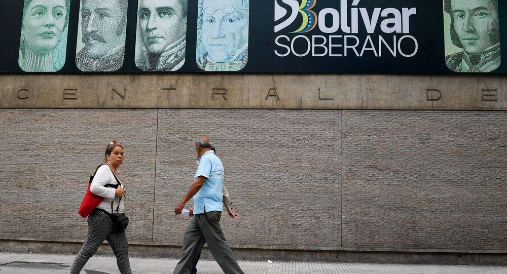 Pessoas caminham junto do Banco Central da Venezuela em Caracas, Venezuela, 13 de junho de 2019