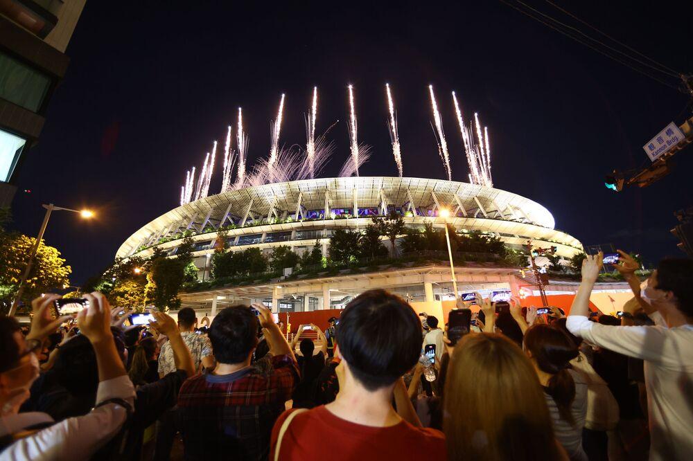 Pessoas fora do estádio assistem aos fogos de artifício durante a cerimônia de encerramento das Olimpíadas de Tóquio