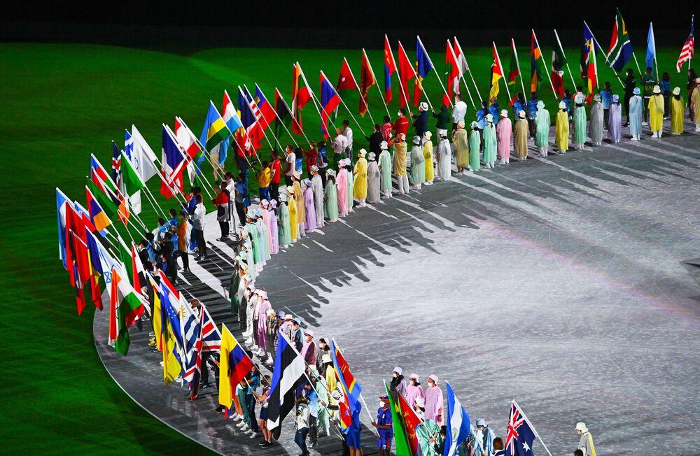 Atletas porta-bandeiras fazem círculo na cerimônia de encerramento dos XXXII Jogos Olímpicos de Verão de Tóquio, no Estádio Olímpico Nacional