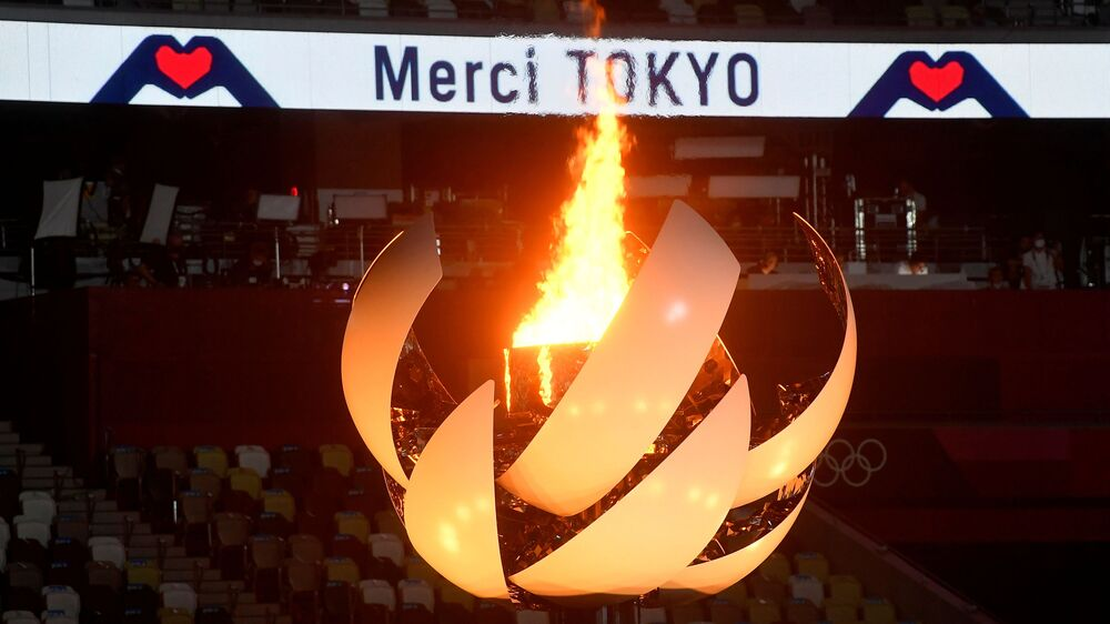 A tocha olímpica e o caldeirão são vistos enquanto mensagens de agradecimento são exibidas durante a cerimônia de encerramento dos Jogos Olímpicos