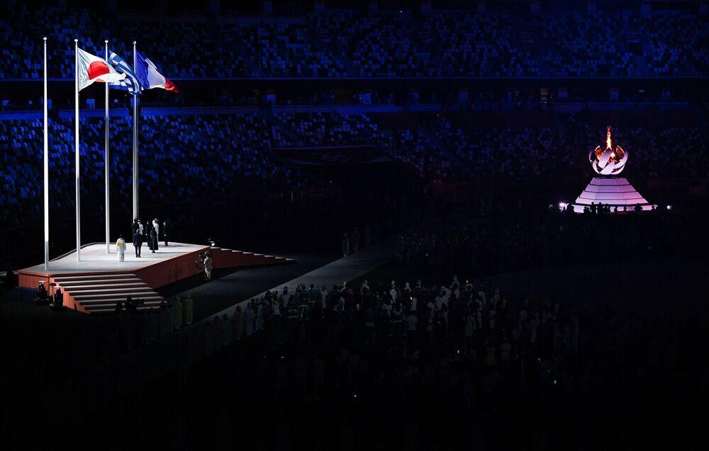 As bandeiras do Japão, Grécia e França são hasteadas durante a cerimônia de encerramento dos XXXII Jogos Olímpicos de Verão em Tóquio
