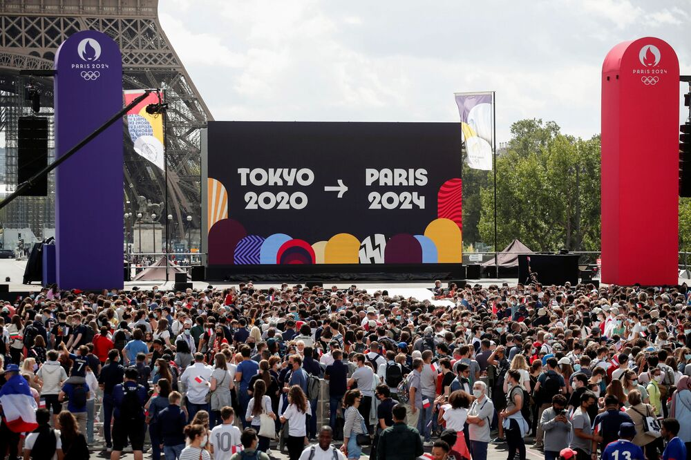 Pessoas assistem à cerimônia de encerramento dos Jogos em Tóquio, em frente à Torre Eiffel em Paris, França