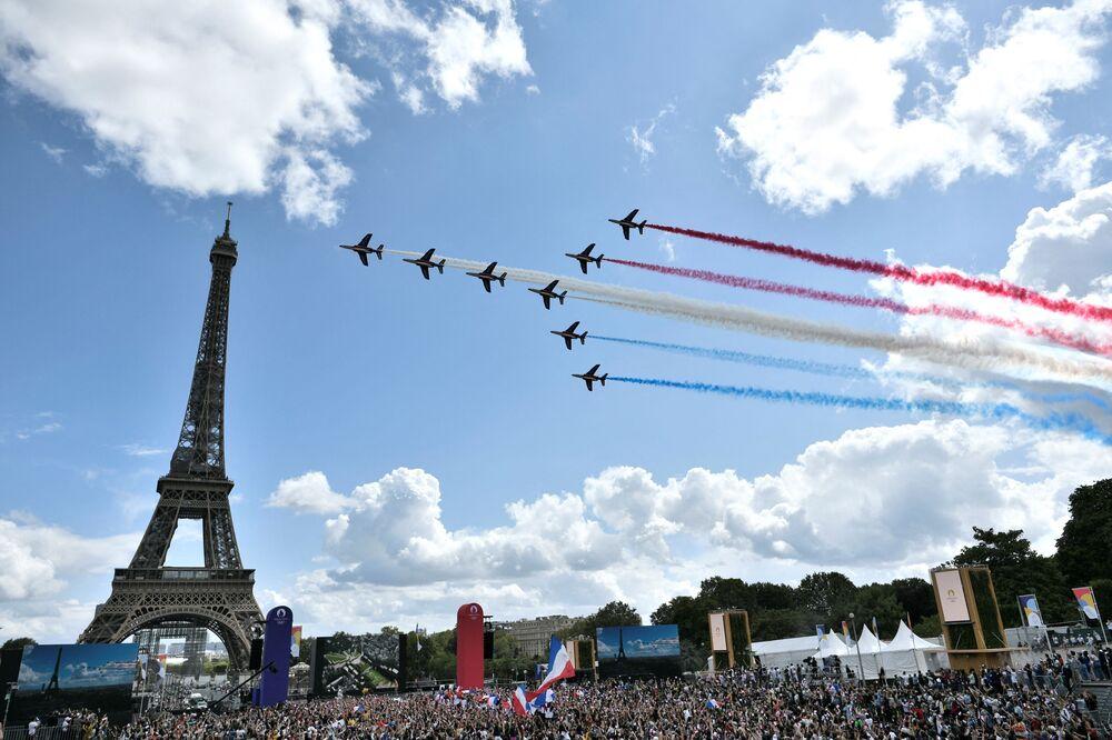 A patrulha aérea francesa sobrevoa fanzone situada em frente à Torre Eiffel, em Paris, após a transmissão da cerimônia de encerramento dos Jogos Olímpicos de Tóquio