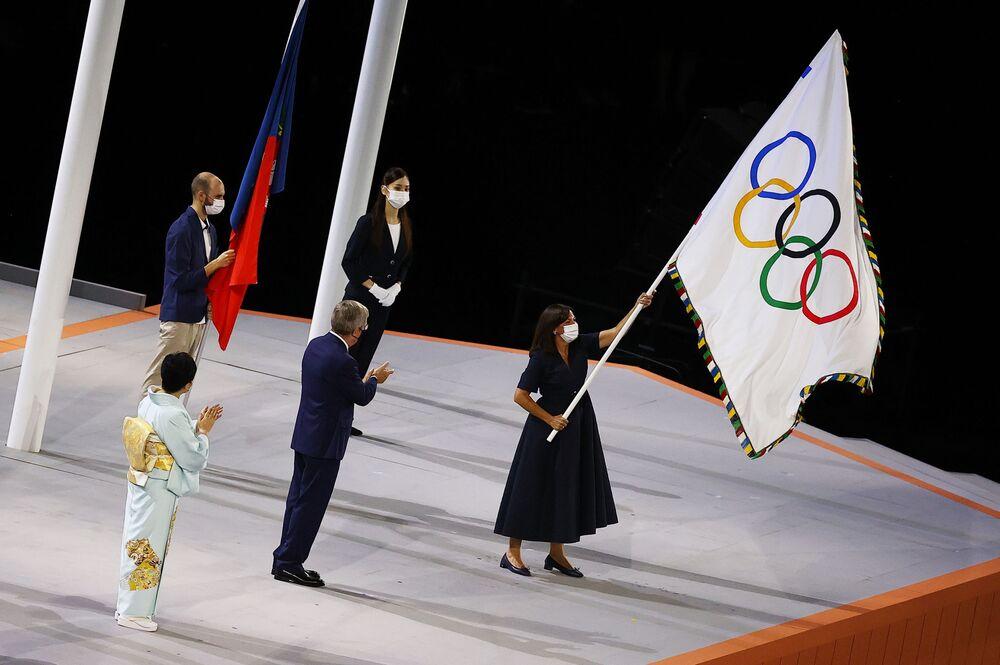 A prefeita de Paris, Anne Hidalgo, agita a bandeira olímpica durante a cerimônia de encerramento dos Jogos Olímpicos de Tóquio enquanto o presidente do Comitê Olímpico Internacional, Thomas Bach, e o governadora de Tóquio, Yuriko Koike, aplaudem
