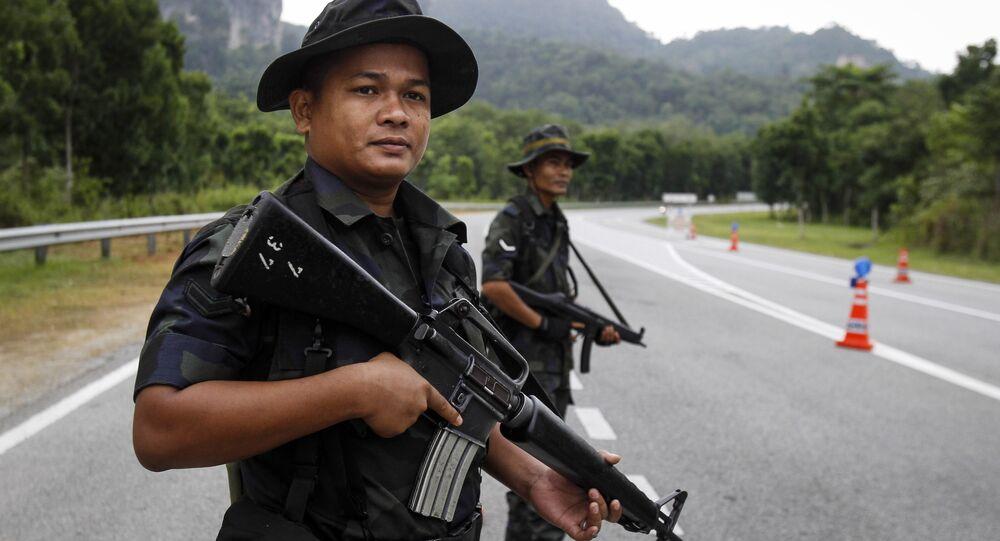 Policiais da Malásia montam guarda na fronteira entre a Malásia e Tailândia