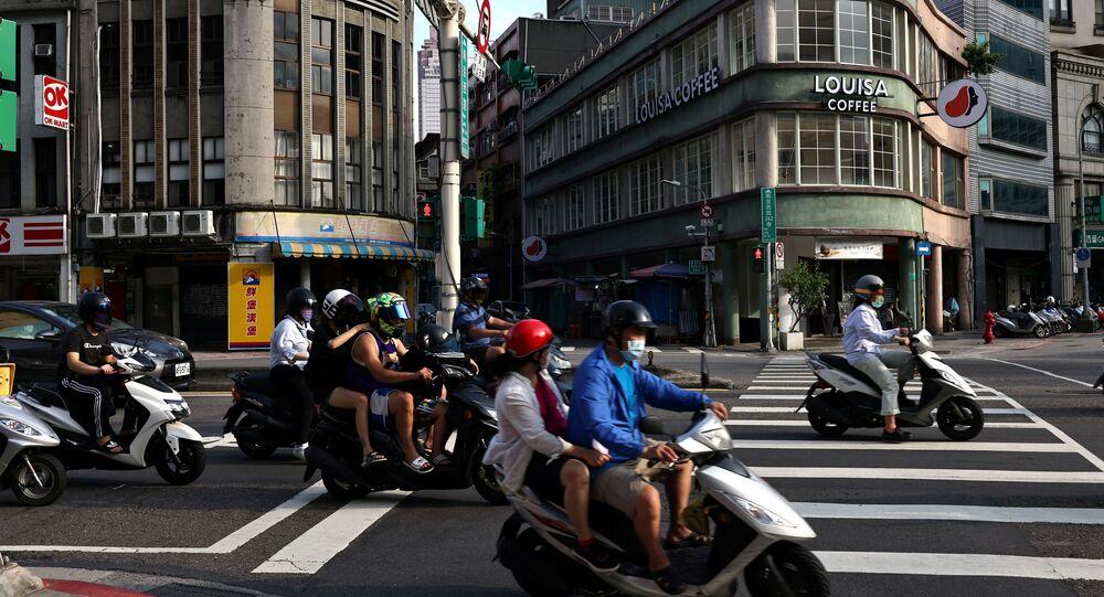 Pessoas usando máscaras dirigem motos em meio à pandemia da doença do coronavírus (COVID-19) em Taipé, Taiwan, 30 de junho de 2021