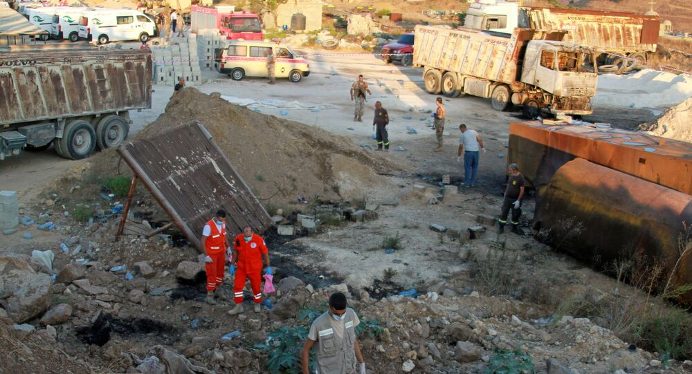 Soldados libaneses, membros da defesa civil e equipes de resgate são vistos no local da explosão do tanque de combustível em Akkar, no norte do Líbano, 15 de agosto de 2021