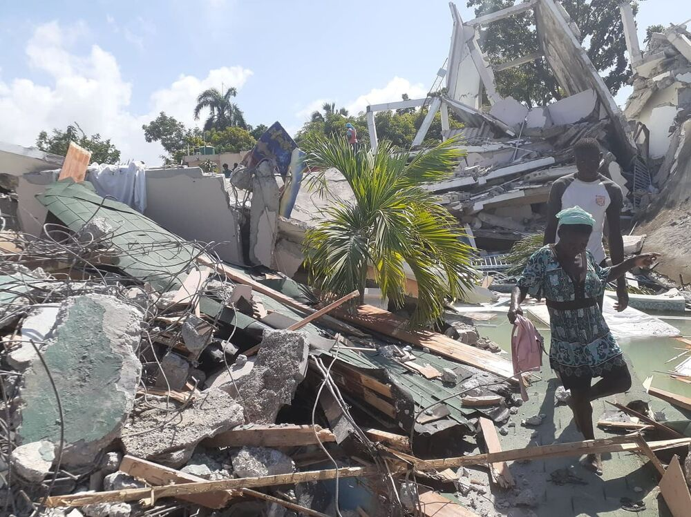 Pessoas caminham por entre os destroços provocados pela força do terremoto, 14 de agosto de 2021