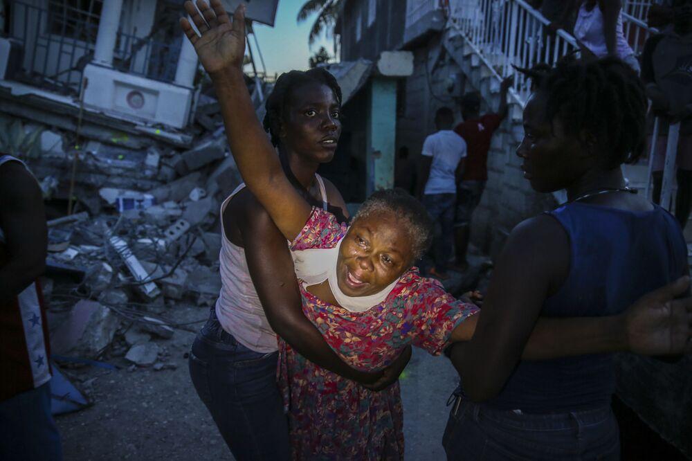Moradora chora após o corpo de sua filha de sete anos ser recuperado de entre os destroços de sua casa abalada pelo terremoto, 14 de agosto de 2021