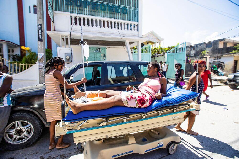 Pessoas transportam uma mulher ferida que sobreviveu à mais recente catástrofe natural no Haiti, 14 de agosto de 2021
