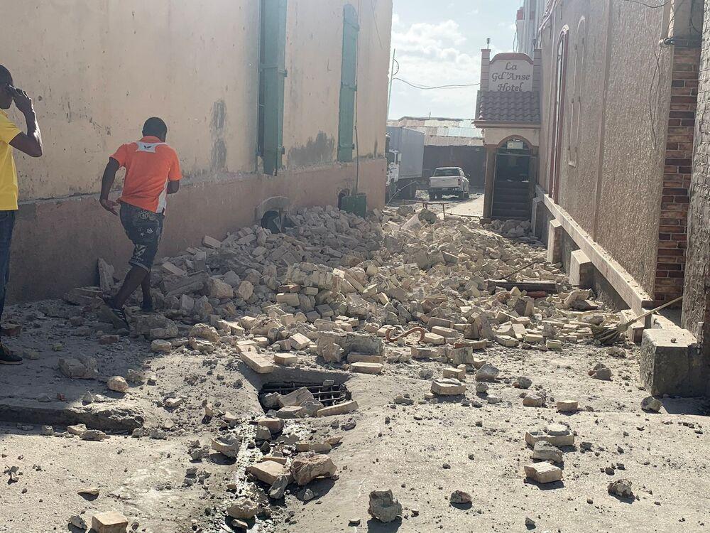 Pessoas caminham com cuidado em uma rua no meio de destroços, 14 de agosto de 2021