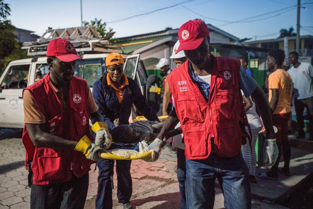 Paramédicos da Cruz Vermelha carregam uma menina ferida, 14 de agosto de 2021