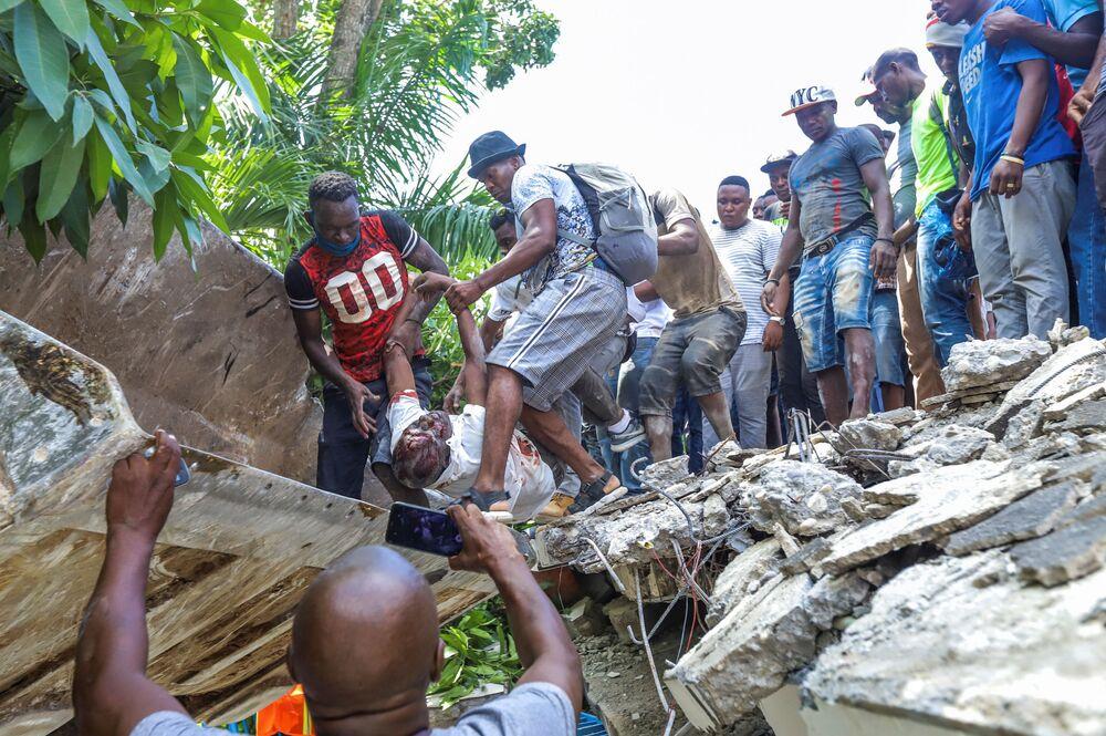 (IMAGEM FORTE) Corpo do político Jean Gabriel Fortune é retirado de entre os destroços de um hotel demolido pelo terremoto, 14 de agosto de 2021