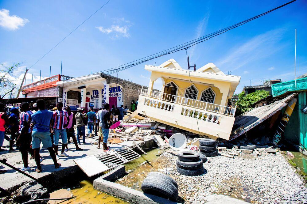 Pessoas param em frente de uma casa destruída pelo terremoto de magnitude 7,2, 14 de agosto de 2021