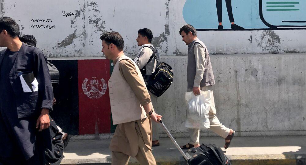 Passageiros afegãos caminham para o aeroporto de Cabul, Afeganistão, 15 de agosto de 2021