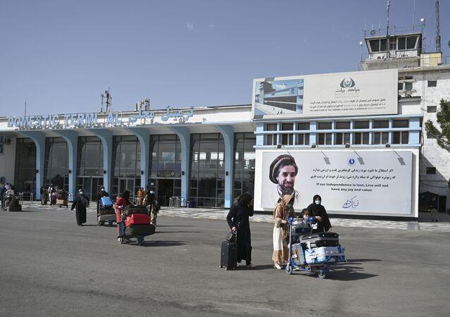 Passageiros afegãos carregam seus pertences quando saem do terminal doméstico no aeroporto de Cabul, em 8 de agosto de 2021