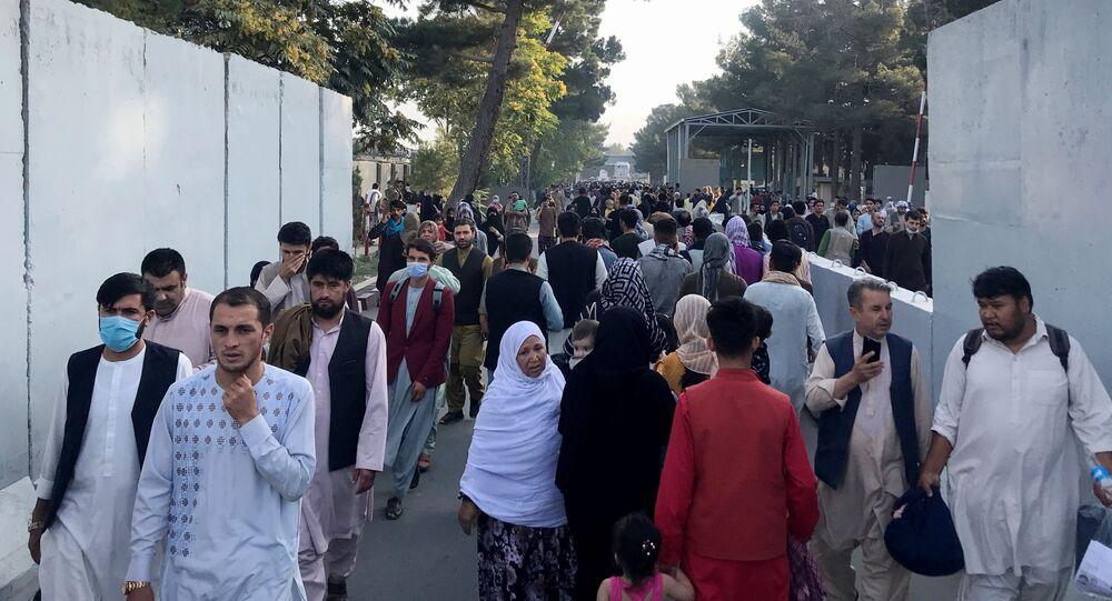 Pessoas caminham na entrada do Aeroporto Internacional de Cabul, Afeganistão