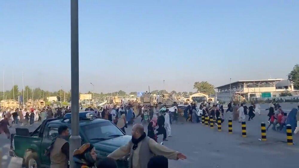 Pessoas correm rumo ao terminal do Aeroporto de Cabul, após os talibãs terem tomado controle sobre o palácio presidencial afegão, 16 de agosto de 2021
