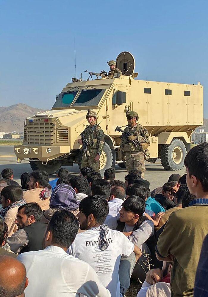 Multidão de afegãos no aeroporto de Cabul em frente de soldados norte-americanos, Afeganistão, 16 de agosto de 2021