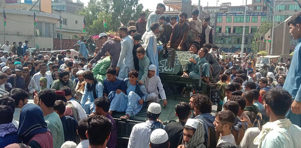 Militantes do Talibã e moradores locais em um veículo Humvee do Exército Nacional do Afeganistão, província de Jalalabad, 15 de agosto de 2021