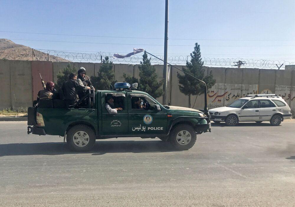 Insurgentes do Talibã em um veículo da polícia em Cabul, 16 de agosto de 2021