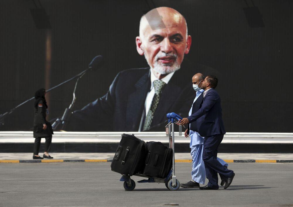 Passageiros caminhando para o terminal de partidas do Aeroporto Internacional Hamid Karzai, 14 de agosto de 2021