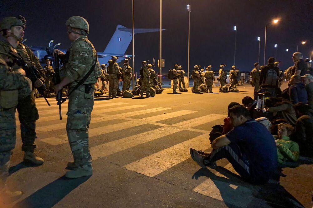 Soldados da França montam guarda enquanto cidadãos franceses e seus companheiros afegãos esperam para embarcar em um avião de transporte militar no aeroporto de Cabul, Afeganistão, 17 de agosto de 2021