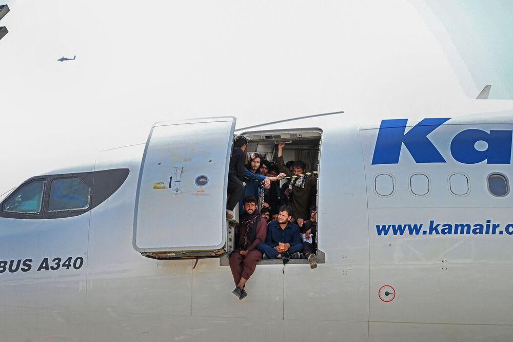 Afegãos sentados à porta de um avião no aeroporto de Cabul, Afeganistão, 16 de agosto de 2021