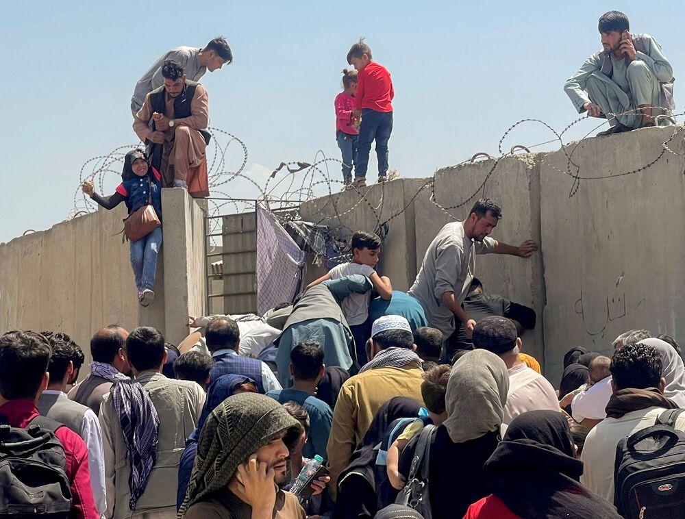 Homem ajuda menina a entrar no Aeroporto Internacional de Hamid Karzai através do muro, enquanto multidões tentam fugir do país, Cabul, Afeganistão, 16 de agosto de 2021