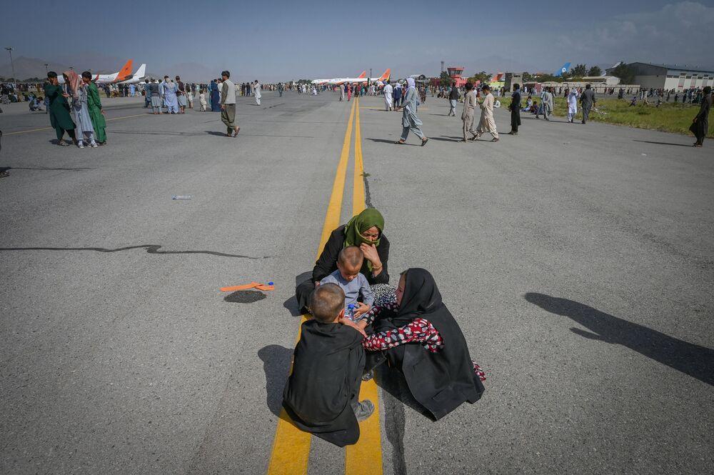 Afegãos sentados na pista esperando sair do país, Cabul, Afeganistão, 16 de agosto de 2021