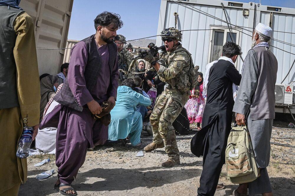 Soldado dos EUA aponta sua arma contra um passageiro afegão no aeroporto de Cabul, Afeganistão, 16 de agosto de 2021