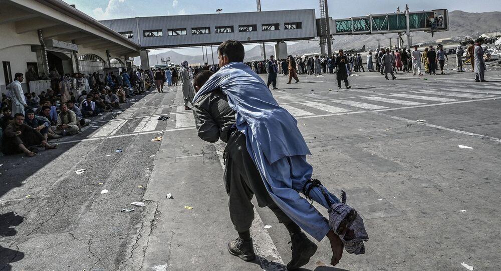 Voluntário carrega um afegão ferido no aeroporto de Cabul, Afeganistão, 16 de agosto de 2021