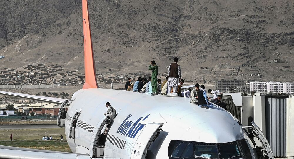 Afegãos sobem ao topo de um avião no aeroporto de Cabul, Afeganistão, 16 de agosto de 2021