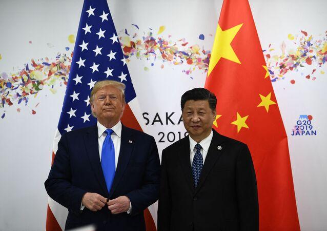 O presidente chinês Xi Jinping (D) e o então presidente dos EUA, Donald Trump, participam de reunião bilateral paralelamente à Cúpula do G20 em Osaka, Japão, em 29 de junho de 2019