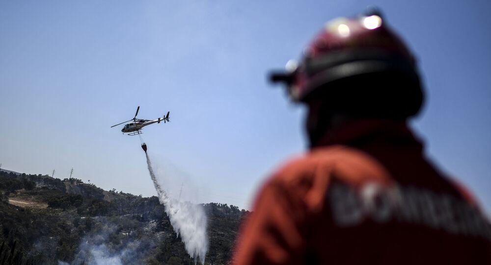 Helicóptero tenta controlar incêndio perto de Tavira, no sul de Portugal, em 17 de agosto de 2021