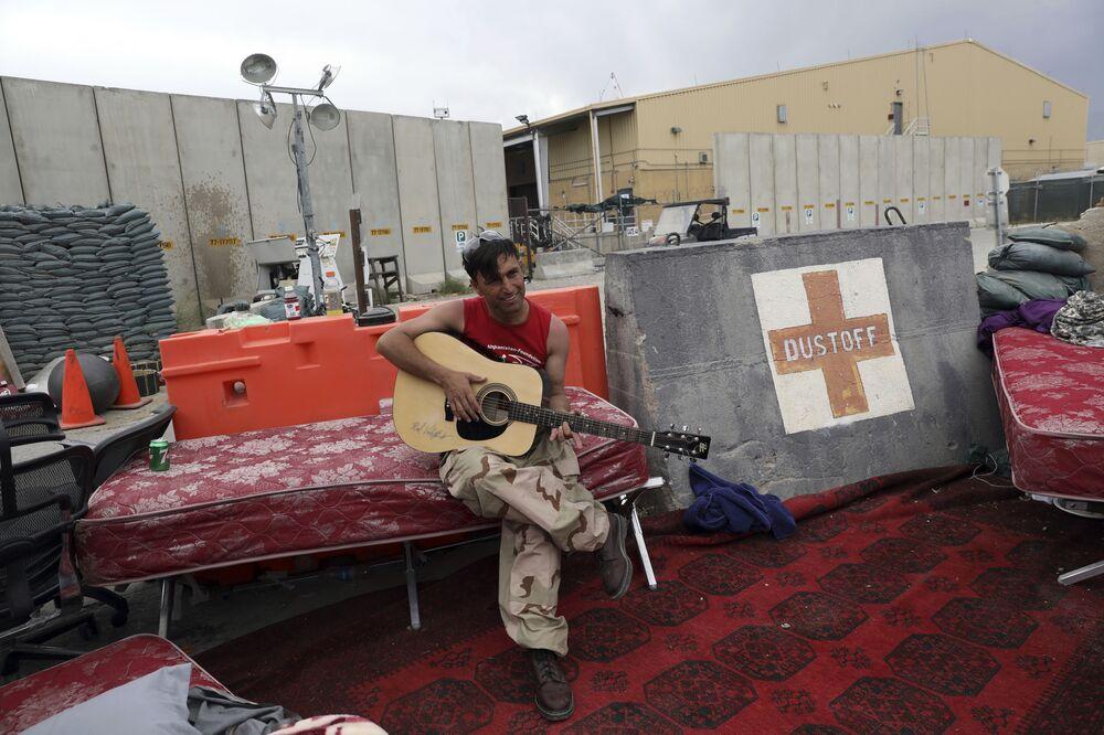 Soldado afegão tocando guitarra na base aérea de Bagram, província de Parwan, Afeganistão, 5 de julho de 2021
