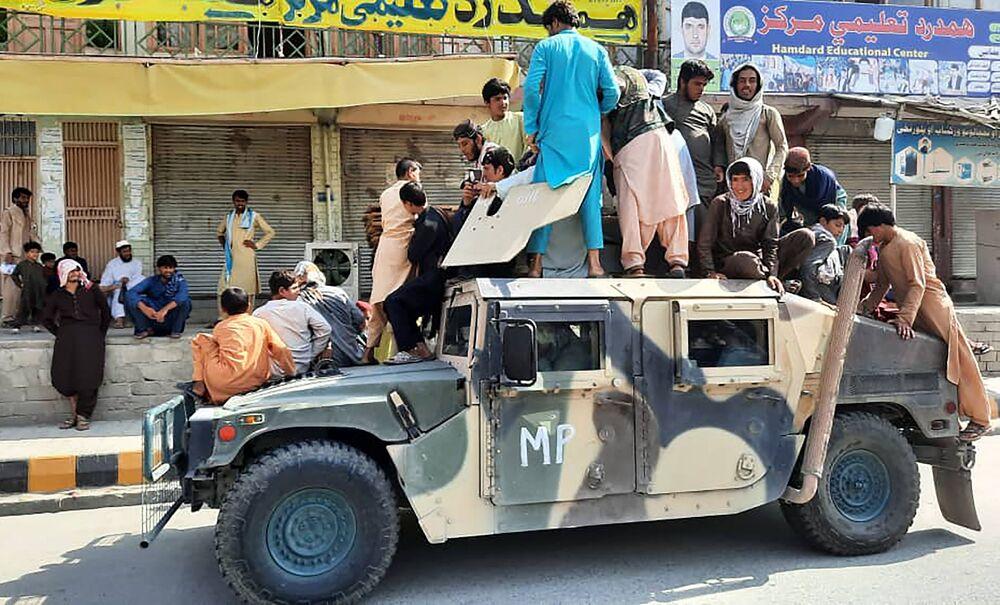 Militantes do Talibã (organização terrorista proibida na Rússia e em vários outros países) e residentes locais sentados em um veículo militar do Exército Nacional Afegão, na província de Laghman, 15 de agosto de 2021
