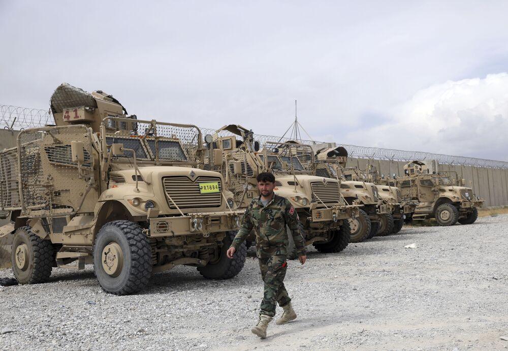 Soldado afegão passa por veículos MRAP (protegidos contra emboscadas e resistentes a minas) que os EUA deixaram na base aérea de Bagram, Afeganistão, 5 de julho de 2021