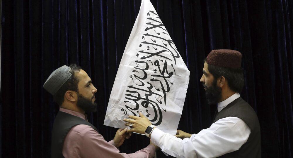 Talibãs arranjam a bandeira do movimento antes da primeira coletiva de imprensa do porta-voz do Talibã, Zabihullah Mujahid, Cabul, Afeganistão, 17 de agosto de 2021