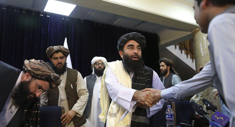 O porta-voz do Taleban, Zabihullah Mujahid, aperta a mão de um jornalista após sua primeira entrevista coletiva, em Cabul, Afeganistão, terça-feira, 17 de agosto de 2021