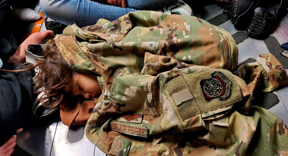 Criança afegã dorme no avião de transporte C-17 Globemaster III da Força Aérea dos EUA, coberta com uniforme do piloto Nicolas Baron, durante o voo de evacuação de Cabul, Afeganistão, 18 de agosto de 2021