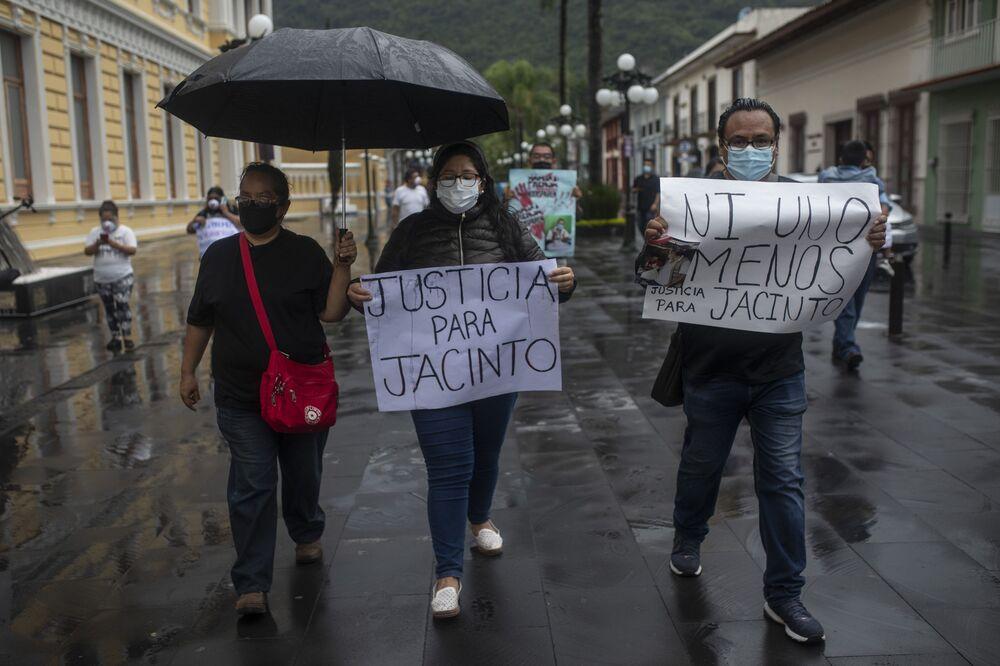 Jornalistas com placas onde está escrito em espanhol Justiça para Jacinto e Nem um a menos. Justiça para Jacinto durante os protestos após a morte de Jacinto Romero Flores, em Orizaba, México, 19 de agosto 2021