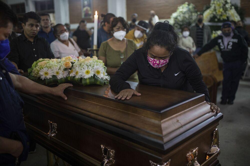 Mulher chorando sobre o caixão do radiojornalista Jacinto Romero Flores, em Ixtaczoquitlán, no estado de Veracruz, México, 19 de agosto de 2021