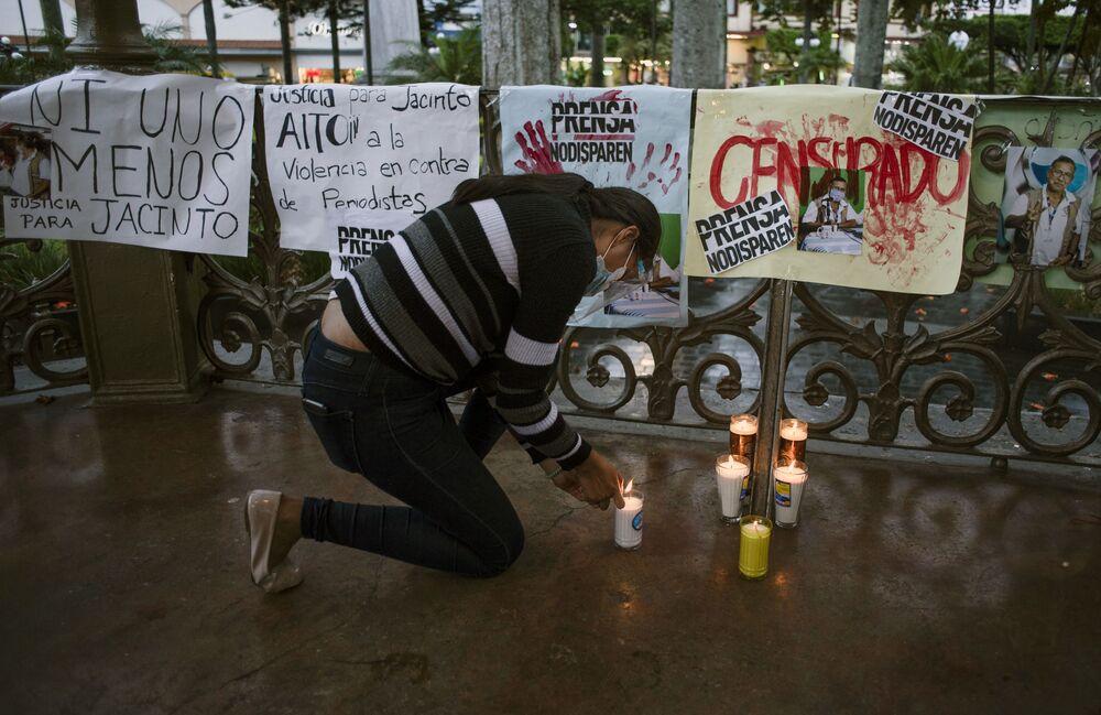 Manifestante contra o homicídio de Jacinto Romero Flores acende uma vela, em Orizaba, México, 19 de agosto 2021