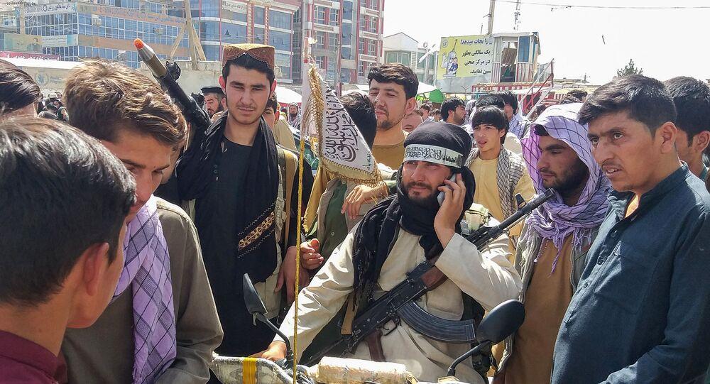 Lutador talibã, na moto, é cercado por moradores em Pul-e-Khumri, Afeganistão, em 11 de agosto de 2021, a cerca de 200 km ao norte de Cabul