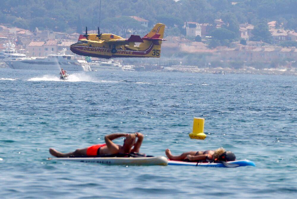 Pessoas descansam enquanto uma aeronave Canadair coleta água para combater um incêndio, França, 17 de agosto de 2021