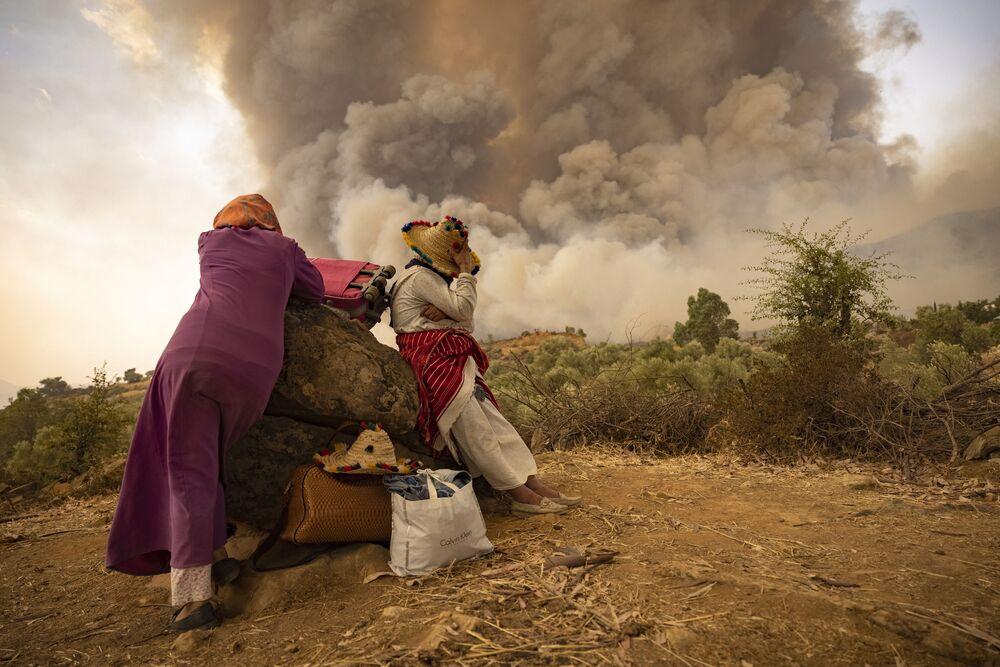 Mulheres marroquinas em estrada de montanha em meio a incêndios florestais no norte do Marrocos, em 15 de agosto de 2021